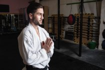 Side view of Man in karate kimono standing with hands in namaste gesture in fitness studio — Stock Photo