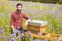 Porträt eines Imkers, der auf einem Bienenstock in einem Blumenfeld sitzt — Stockfoto