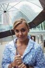 Retrato de una hermosa mujer sosteniendo el paraguas durante la temporada de lluvias y mirando a la cámara - foto de stock