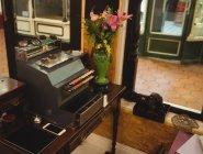 Velha máquina de escrever e vaso no balcão na loja — Fotografia de Stock