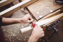 Человек с помощью ручного инструмента, чтобы сгладить и выровнять поверхность доски на лодочной станции — стоковое фото