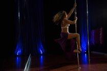 Hermosa bailarina polaca practicando pole dance en estudio - foto de stock