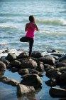 Вид сзади женщины, занимающейся йогой на камнях в солнечный день — стоковое фото