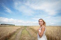 Bonita mulher loira de pé no campo e olhando para a câmera — Fotografia de Stock