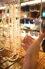 Hand of woman selecting jewellery in a antique jewellery shop — Stock Photo
