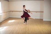 Partenaires de ballet hommes et femmes dansant ensemble dans un studio moderne — Photo de stock