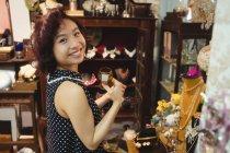 Retrato de mulher sorridente selecionando uma xícara em lojas de joalharia antiga — Fotografia de Stock