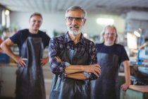 Portrait of mature male glassblowers at glassblowing factory — Stock Photo