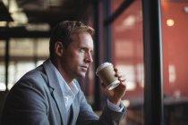 Задумчивый бизнесмен пьет кофе в кафе — стоковое фото