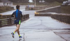 Athlete running on road during the day — Stock Photo