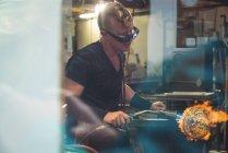 Митець, даючи остаточний доторкнутися до шматка скла з glassblowing факел на заводі glassblowing — стокове фото