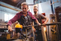 Glassblowers forming and shaping a molten glass at glassblowing factory — Stock Photo