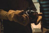 Стеклодув держит стеклянную чашу на стеклодувном заводе — стоковое фото