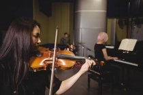 Due studentesse che suonano violino e pianoforte in uno studio — Foto stock