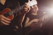 Schöne Frauen, die in der Musikschule Gitarre spielen — Stockfoto