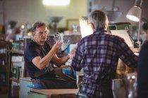 Митець показ скляній вазі колега, glassblowing заводу — стокове фото
