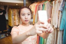 Woman taking selfie from mobile phone at boutique store — Stock Photo