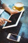 Close-up de mulher usando tablet digital enquanto toma café no café — Fotografia de Stock