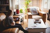 Беременная женщина смотрит на снимок УЗИ на планшете в гостиной — стоковое фото
