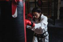 Селективное внимание женщины, практикующей карате с боксерской грушей в фитнес-студии — стоковое фото