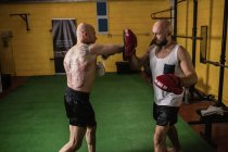 Side view of two thai boxers practicing in gym — Stock Photo