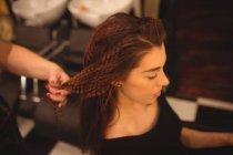 Schöne Frau stylt ihre Haare im Salon — Stockfoto
