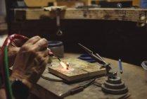Руки ремесленницы с помощью паяльника в мастерской — стоковое фото