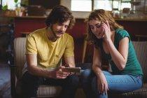 Механіки, сидячи на дивані і використання мобільного телефону у майстерні — стокове фото