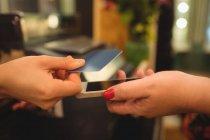 Client donnant téléphone et carte de crédit au caissier au comptoir de facturation — Photo de stock