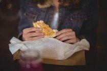 A meio da seção da mulher sentada à mesa e comendo sanduíche na loja de bicicletas — Fotografia de Stock