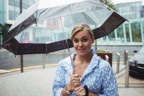 Retrato de mujer atractiva sosteniendo paraguas durante la temporada de lluvias - foto de stock