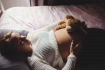 Высокий угол обзора Беременная женщина держит плюшевого медведя на животе во время сна в спальне дома — стоковое фото
