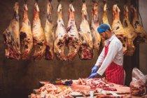 Açougueiro corta carne na arrecadação do talho — Fotografia de Stock