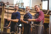 Portrait of team of glassblowers shaping a glass on the blowpipes at glassblowing factory — Stock Photo