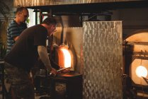 Team of glassblowers heating glass in furnace at glassblowing factory — Stock Photo