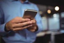 Средняя секция бизнесмена с помощью мобильного телефона в офисе — стоковое фото