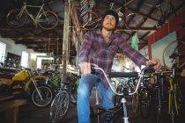 Mecânico atencioso sentado na bicicleta na loja de bicicletas — Fotografia de Stock