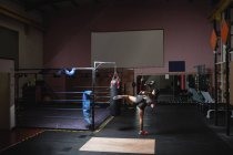 Back view of Female boxer kicking punching bag in fitness studio — Stock Photo