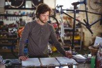 Escrita mecânica na área de transferência no balcão na loja de bicicletas — Fotografia de Stock