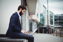 Uomo d'affari attento utilizzando laptop al di fuori dell'ufficio — Foto stock