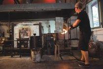 Митець опалення скла в печі при glassblowing заводу — стокове фото