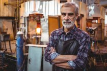 Портрет стеклодува со скрещенными руками на стекольном заводе — стоковое фото