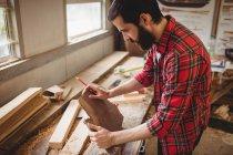 Mann arbeitet auf Bootswerft über Holzplanke — Stockfoto