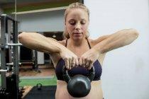 Беременная женщина поднимает колокольчик в спортзале — стоковое фото