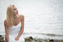 Unbeschwerte blonde Frau kauert in der Nähe von Fluss und wegsehen — Stockfoto