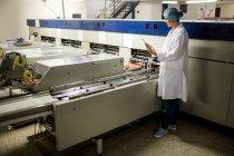 Personnel féminin utilisant une tablette numérique à côté de la ligne de production dans l'usine d'œufs — Photo de stock