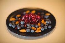 Granada, arándano y almendra en un plato sobre mesa de madera - foto de stock