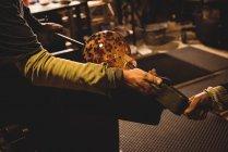 Команда стеклодувов формирует расплавленное стекло на стекольном заводе — стоковое фото
