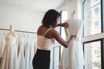 Female fashion designer adjusting the dress on a mannequin in the studio — Stock Photo