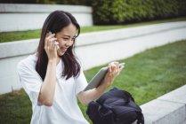Jeune femme parlant sur téléphone portable tout en utilisant une tablette numérique dans le jardin — Photo de stock